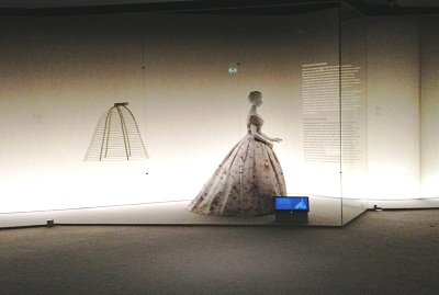 View of a mid-19th century crinoline and dress on the second floor of Fashioning Fashion