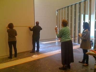 Curator Ilene Susan Fort, graphic designer Jin Son, exhibition designer Victoria Behner, environmental designer Daniel Young discussing the installation progress; Behner, Time Based Media Exhibition Manager Eddy Vajarakitipongse, curator Ilene Susan Fort and Curatorial Assistant Marvella Muro deciding where the exterior for the film should go