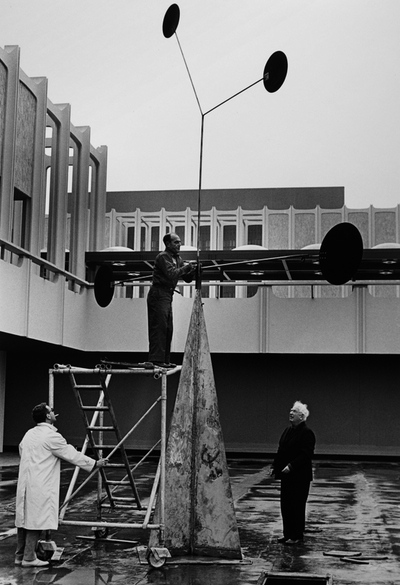 Alexander Calder and ironworker Chippy Ieronimo overseeing the installation of Three Quintains (Hello Girls), 1964, photo © 2013 Museum Associates/LACMA, photographic archives