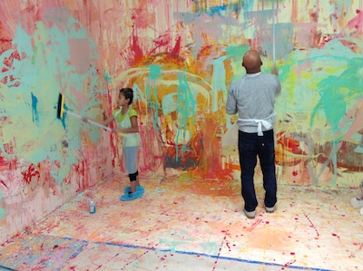 Artist Kaz Oshiro works with a student on a collaborative painting project.