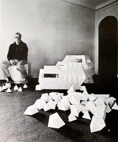 Tony Smith next to a model composed of tetrahedrons and octahedrons (with additional maquette modules in the foreground) [Photographer: Malcolm Lubliner]