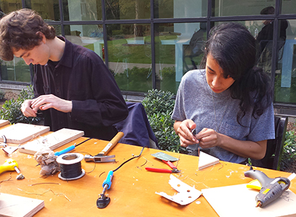Derelict Electronics participants at work on amplifiers and solar cells.