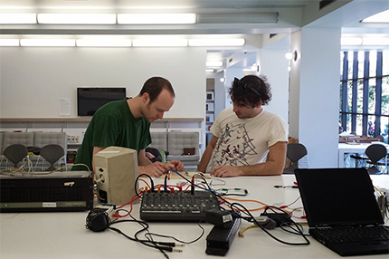 Artist Ryan Jordan and a workshop participant test an amplifier.