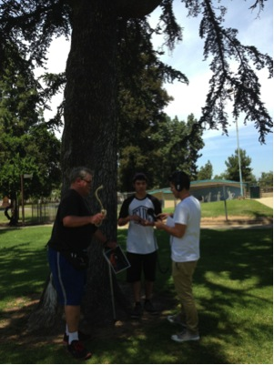 Image Caption: Temperatures were over 100 degrees that day, so groups huddled under trees and tents to rehearse and record their soundscape. Educator: Fernando Cervantes
